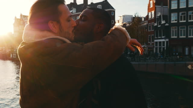 adult gay couple enjoying city break in amsterdam, having fun, kissing and loving each other - omosessualità video stock e b–roll