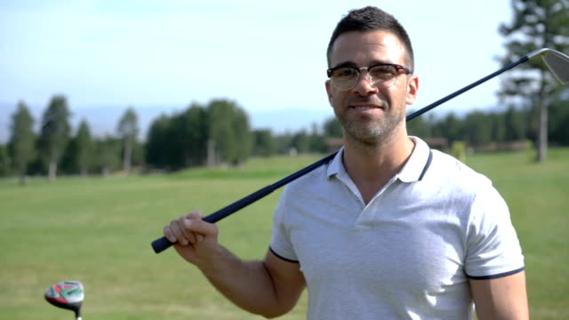 adult golf player smiling at camera - figura maschile video stock e b–roll