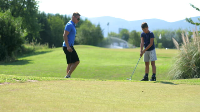 vídeos de stock e filmes b-roll de adult golfer teaching a boy how to play golf - golfe