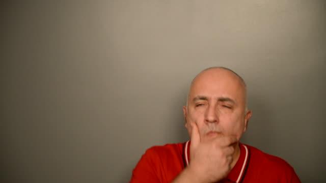 vidéos et rushes de adulte à poils gris homme sur un fond gris.  les doutes. - vidéo portrait