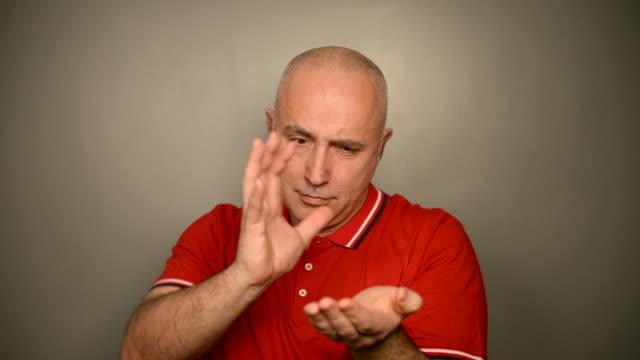 vidéos et rushes de adulte à poils gris homme avec apple sur un fond gris. - vidéo portrait