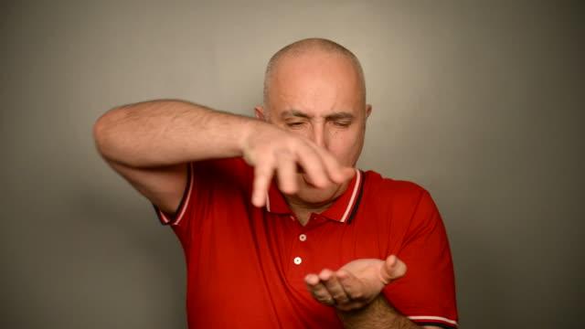vídeos de stock, filmes e b-roll de de pêlo adulto homem grisalho com maçã sobre um fundo cinza. - truque de mágica