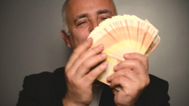 adulto gray a pelo uomo con denaro su sfondo grigio. - pensionati lavoratori video stock e b–roll