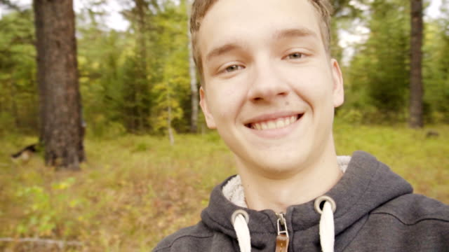 vídeos de stock, filmes e b-roll de adult guy in a good mood is walking in the forest and smiling - meninos adolescentes