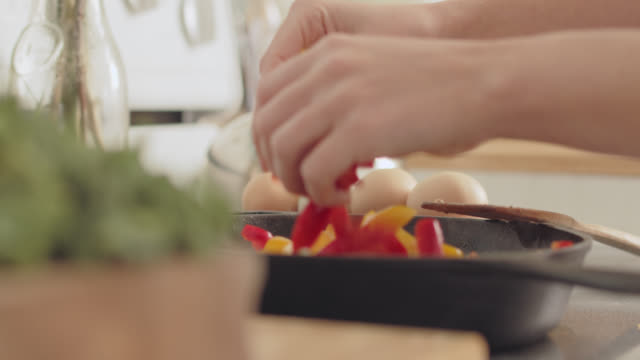 vídeos de stock, filmes e b-roll de cu of adult hands placing fresh peppers into a pan - skillet cooking pan