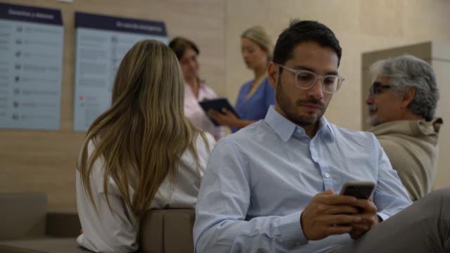 vidéos et rushes de adulte bel homme textos sur le smartphone tout en s'asseyant sur la salle d'attente à l'hôpital - salle d'attente