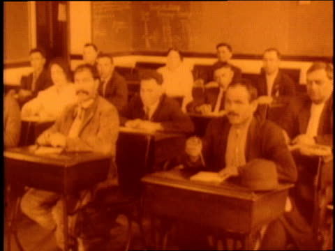 adult immigrants learn english in a classroom. - anno 1910 video stock e b–roll