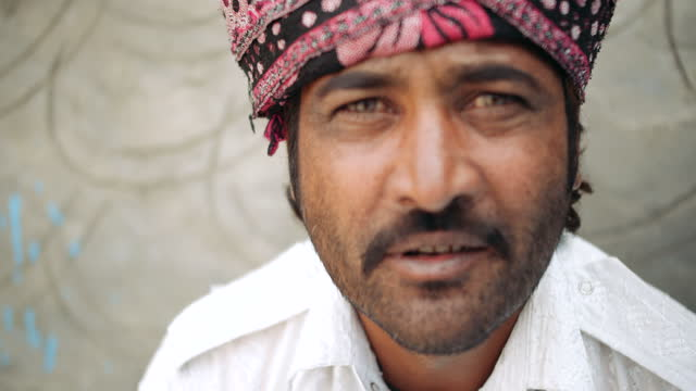 adult indian male with turban looks at camera- talks and smiles - human face video stock e b–roll