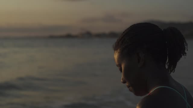 adult jamaican female surfer looks out onto sea - jamaican ethnicity stock videos and b-roll footage