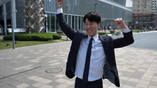 vidéos et rushes de homme d'affaires coréen adulte célébrant la promotion - quartier