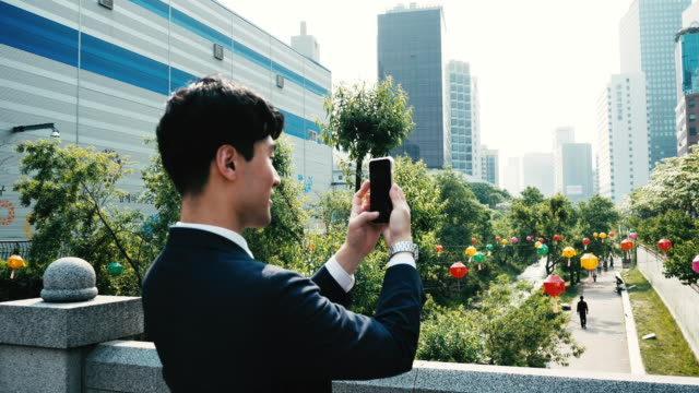 adult korean businessman using mobile phone during business travel - one mid adult man only stock videos & royalty-free footage