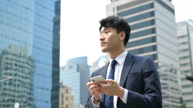 vidéos et rushes de homme d'affaires coréen adulte utilisant le téléphone portable près de l'immeuble de bureaux - costume complet