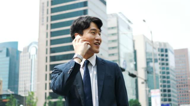 vídeos y material grabado en eventos de stock de empresario coreano adulto usando teléfono móvil cerca de la construcción de oficinas - coreano oriental