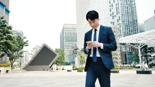 オフィスビル近くで携帯電話を使う大人の韓国人ビジネスマン - 朝鮮半島点の映像素材/bロール