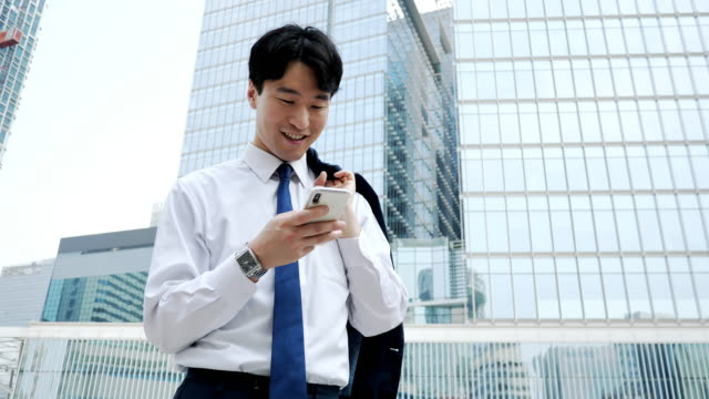 adult korean businessman using mobile phone near office building - one mid adult man only stock videos & royalty-free footage
