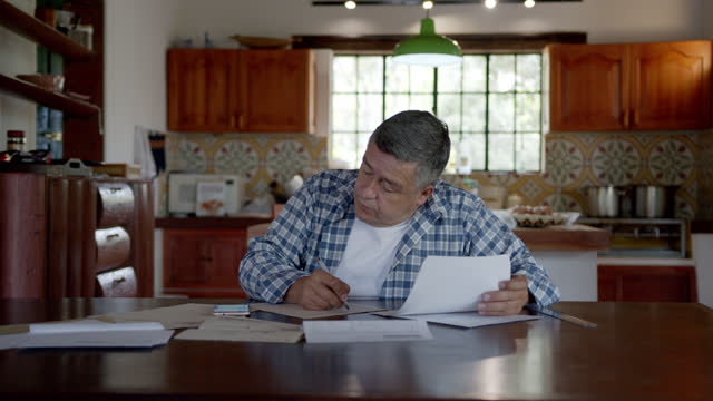 vídeos de stock e filmes b-roll de adult latin american man organizing his finances at his house in the countryside using the calculator on smartphone - latin american and hispanic ethnicity