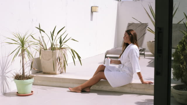 adult latin/hispanic woman relaxing at home in sunshine - one mid adult woman only stock videos & royalty-free footage