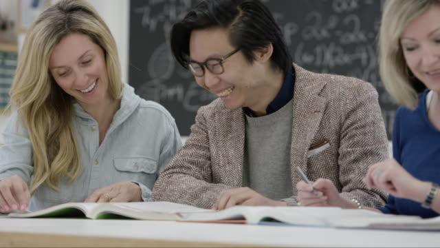 vuxna manliga och kvinnliga studenter studera tillsammans - teknisk högskola bildbanksvideor och videomaterial från bakom kulisserna