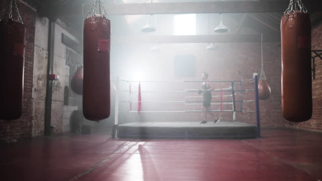 adult male boxer stepping into the ring - 格闘技リング点の映像素材/bロール
