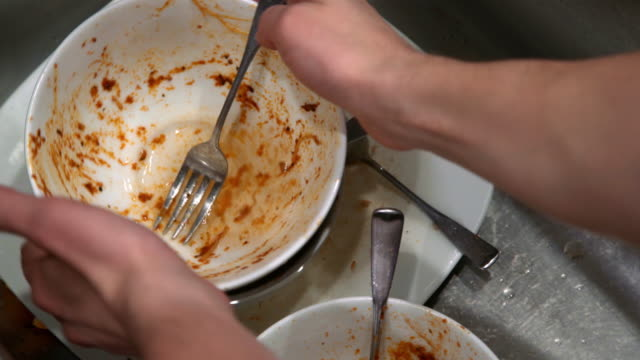 vídeos de stock, filmes e b-roll de mãos caucasianas masculinas adultas preparando pratos sujos após almôndegas de espaguete e jantar de molho vermelho - lavando louça