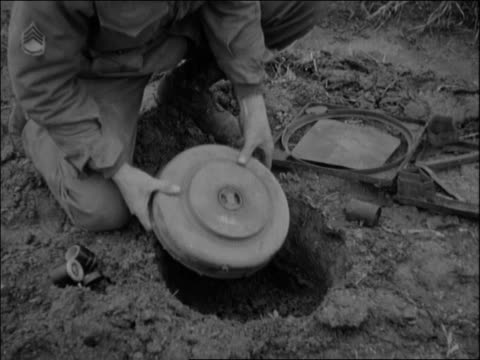 vídeos de stock e filmes b-roll de adult male caucasian us army soldier digging hole adult male caucasian staff sergeant lowers land mine into hole carefully places in detonator and... - enterrado
