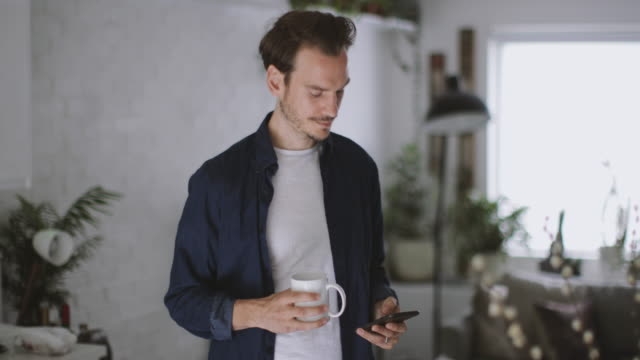 adult male checking smartphone in kitchen with mug of coffee - bildserie bildbanksvideor och videomaterial från bakom kulisserna