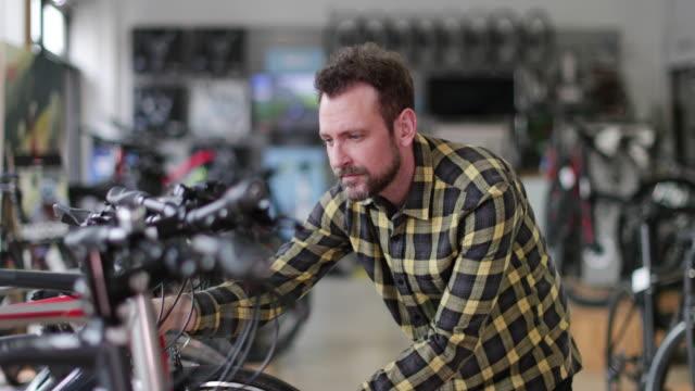 vídeos y material grabado en eventos de stock de adult male choosing a bike in a cycle store - vehículo de propulsión humana