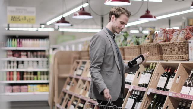vídeos y material grabado en eventos de stock de adult male choosing wine in grocery store - botella de vino
