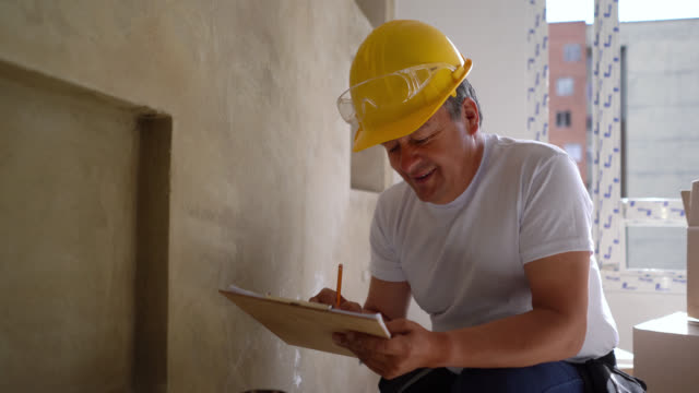 adult male contractor planning on clipboard at a home improvement and then facing camera smiling - craftsperson stock videos & royalty-free footage