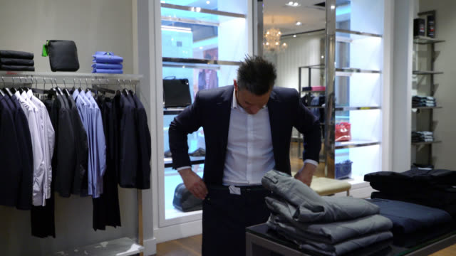 adult male customer looking at pants at a formalwear store - all shirts stock videos & royalty-free footage