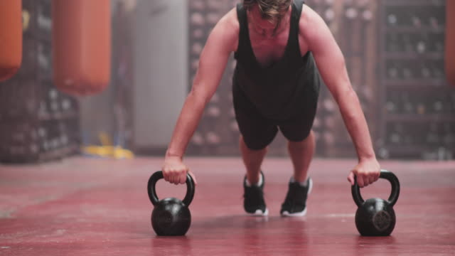 adult male doing dumbbell pushups at the gym - smooth stock videos & royalty-free footage