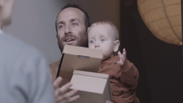 vídeos y material grabado en eventos de stock de adult male father receiving and signing for parcels at front door - recibir