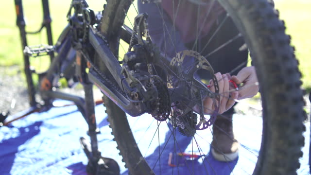 adult male fixes mountain bike on alpine road - mountain bike stock videos and b-roll footage
