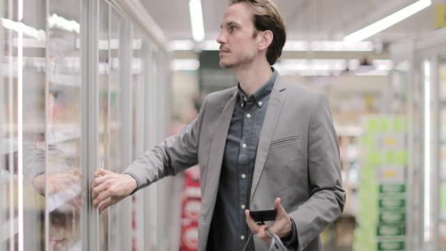 vidéos et rushes de adult male grocery shopping - panier courses
