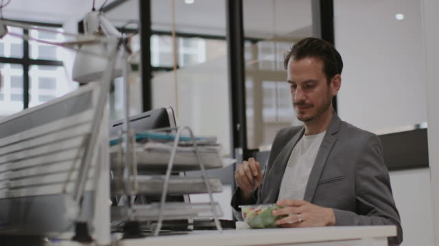 adult male having lunch whilst working at desk in office - lunch stock videos & royalty-free footage