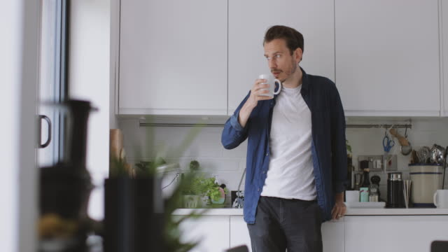 Adult male having morning coffee in kitchen