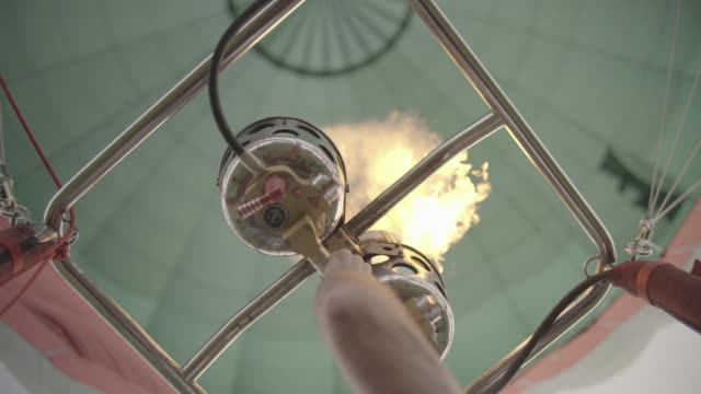 adult male initiates burner in hot air balloon, shoots flames to heat air - balloon stock videos & royalty-free footage