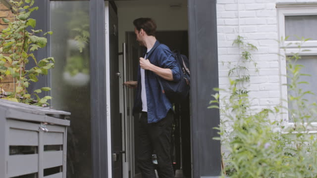 vidéos et rushes de adult male leaving the house and checking smartphone - house