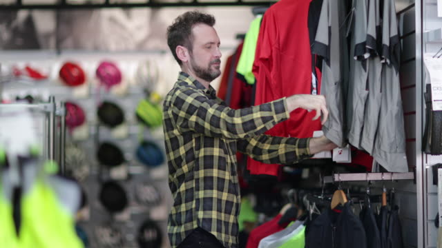 adult male looking at sportswear in store - sportkleidung stock-videos und b-roll-filmmaterial