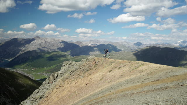 Vuxna manlig mountainbikecyklist balanserar cykel på alpine ridge
