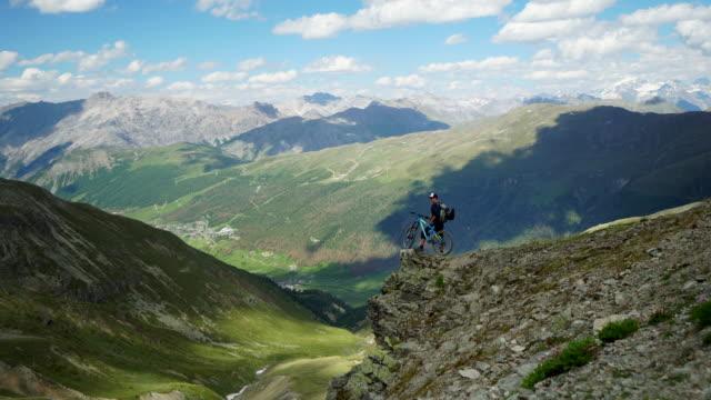 Vuxna manlig mountainbikecyklist vilar på Alpin lookout ovan gröna dalen