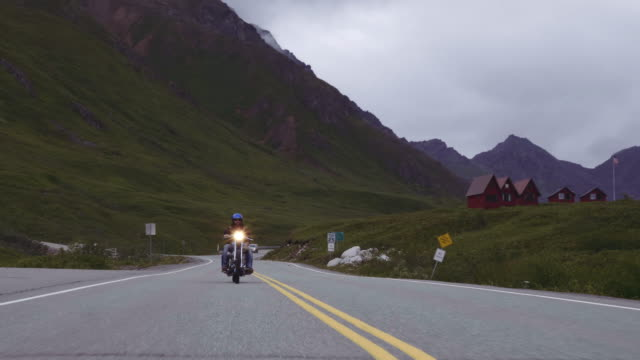 UHD 4K: Adult male on a motorcycle riding down a scenic highway