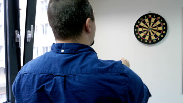Adult male playing darts in the office