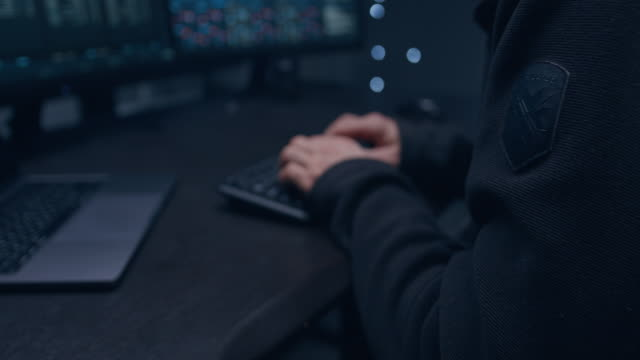 adult male programmer in a dark hoodie with the hood writing code. it tracks virus attacks on a large monitor. - information medium stock videos & royalty-free footage