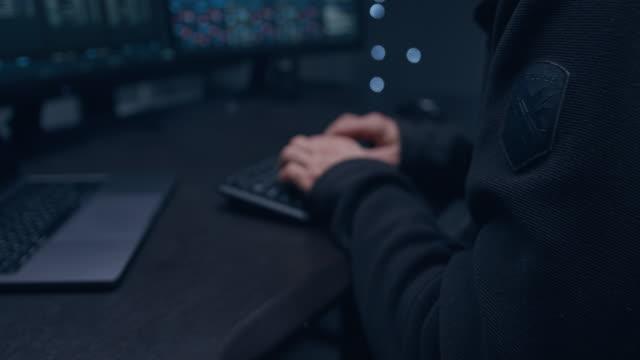 vuxen manlig programmerare i en mörk hoodie med huven skrivkod. den spårar virusattacker på en stor bildskärm. - informationsmedium bildbanksvideor och videomaterial från bakom kulisserna