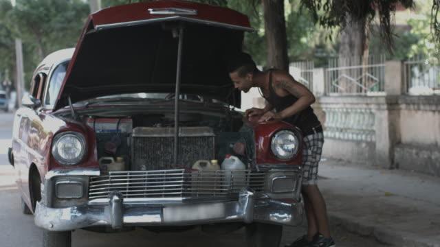 Adult male repairing broken down car in street Havana, Cuba