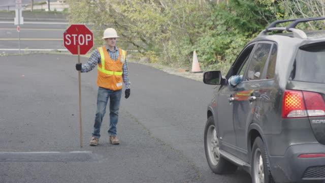 vidéos et rushes de flagger route mâle adulte est joyeusement en baisse un véhicule sur une route de quartier - âges mélangés