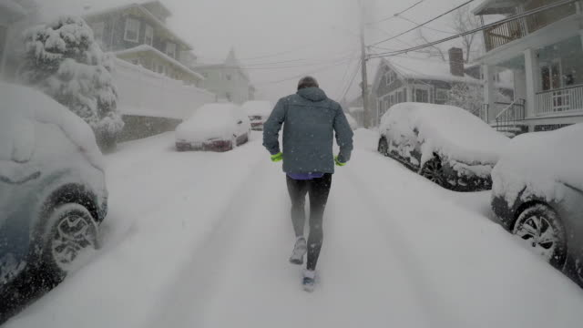 Adult male runs up snow-covered city street during snowstorm