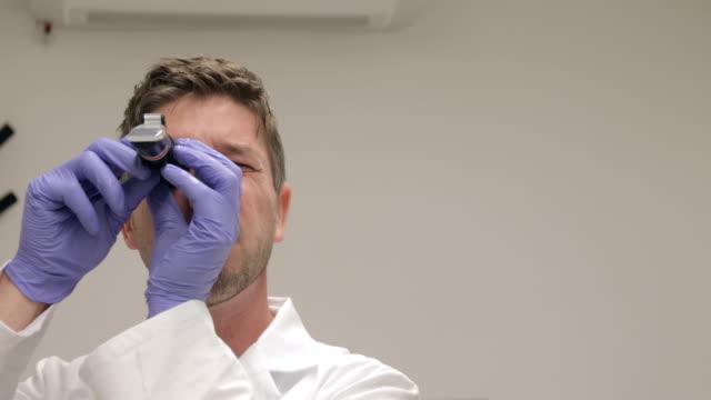 erwachsene männliche wissenschaftler mit refraktometer zur maßnahme zuckergehalt in traube - wissenschaftliches experiment stock-videos und b-roll-filmmaterial