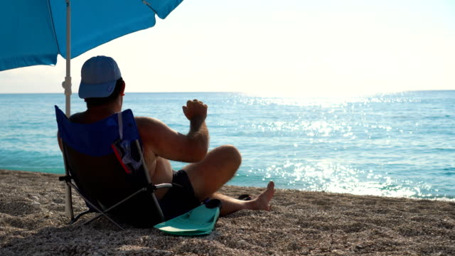 adult male sitting on beach chair and enjoying sea view and sea breeze - mid adult men stock videos & royalty-free footage